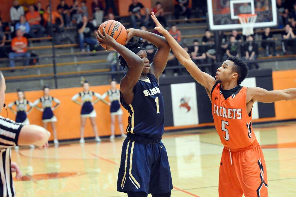 Chester's Demontae Martin (right) defends Saxony Lutheran's William Rogers in the second quarter of the Crusaders' win over the Yellow Jackets. Rogers scored a game-high 15 points and was named the MVP of the tournament.