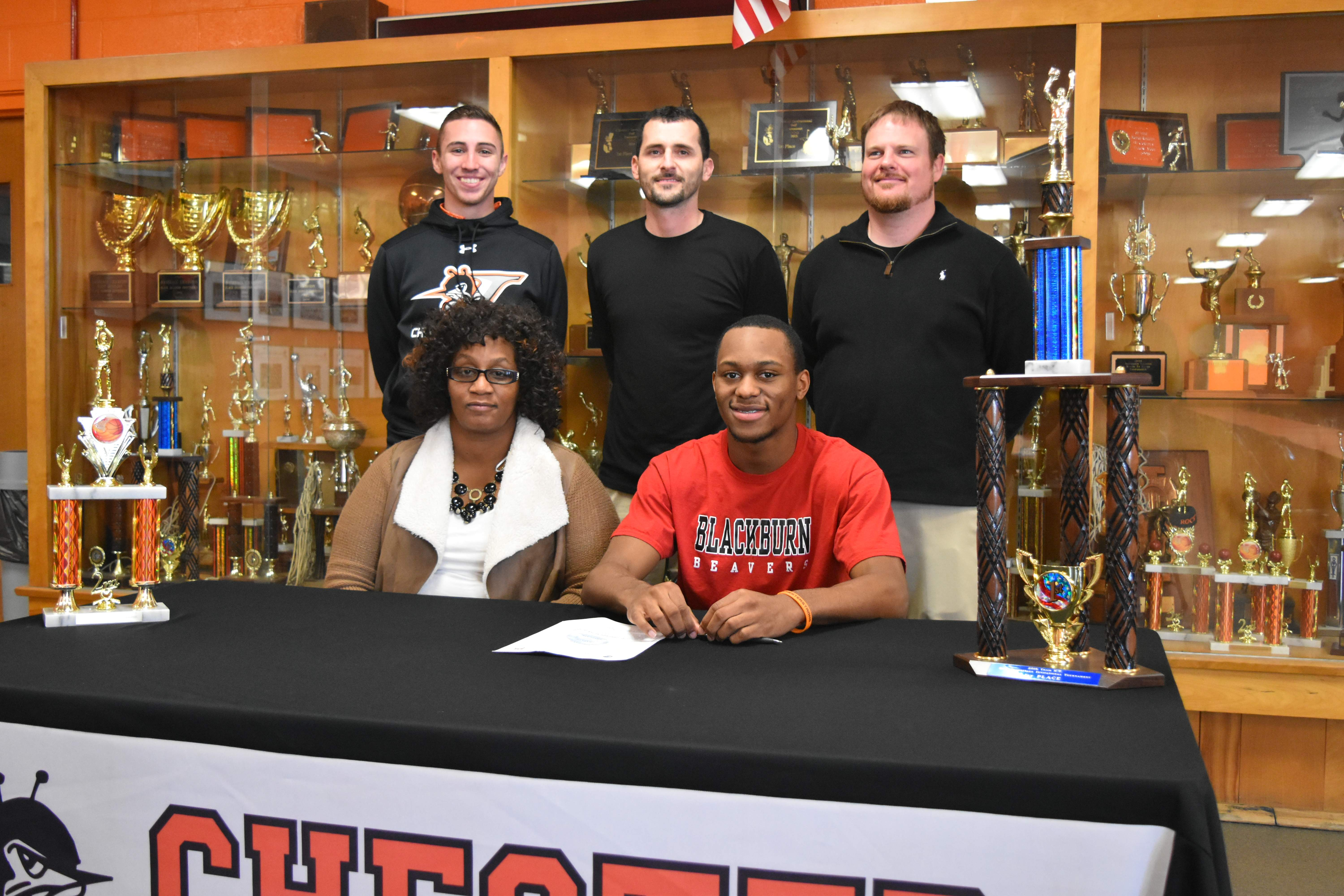 Chester senior Savion Smith (front row, right) signed a national letter-of-intent on Wednesday to play basketball for Blackburn College. Pictured with Smith is his mother, Debrah Merriweather (front row, left), assistant football coach Jake Cowan (back row, left), boys head basketball coach Brad Norman (back row, center) and assistant football coach Ben Hunter (back row, right).