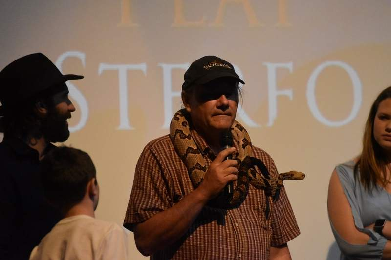 "Tony Gerard, a biologist and animal handler for ""Dig Two Graves,"" talks to the audience while Sintullo, a large timber rattlesnake featured in the film, drapes across Gerard's shoulders."