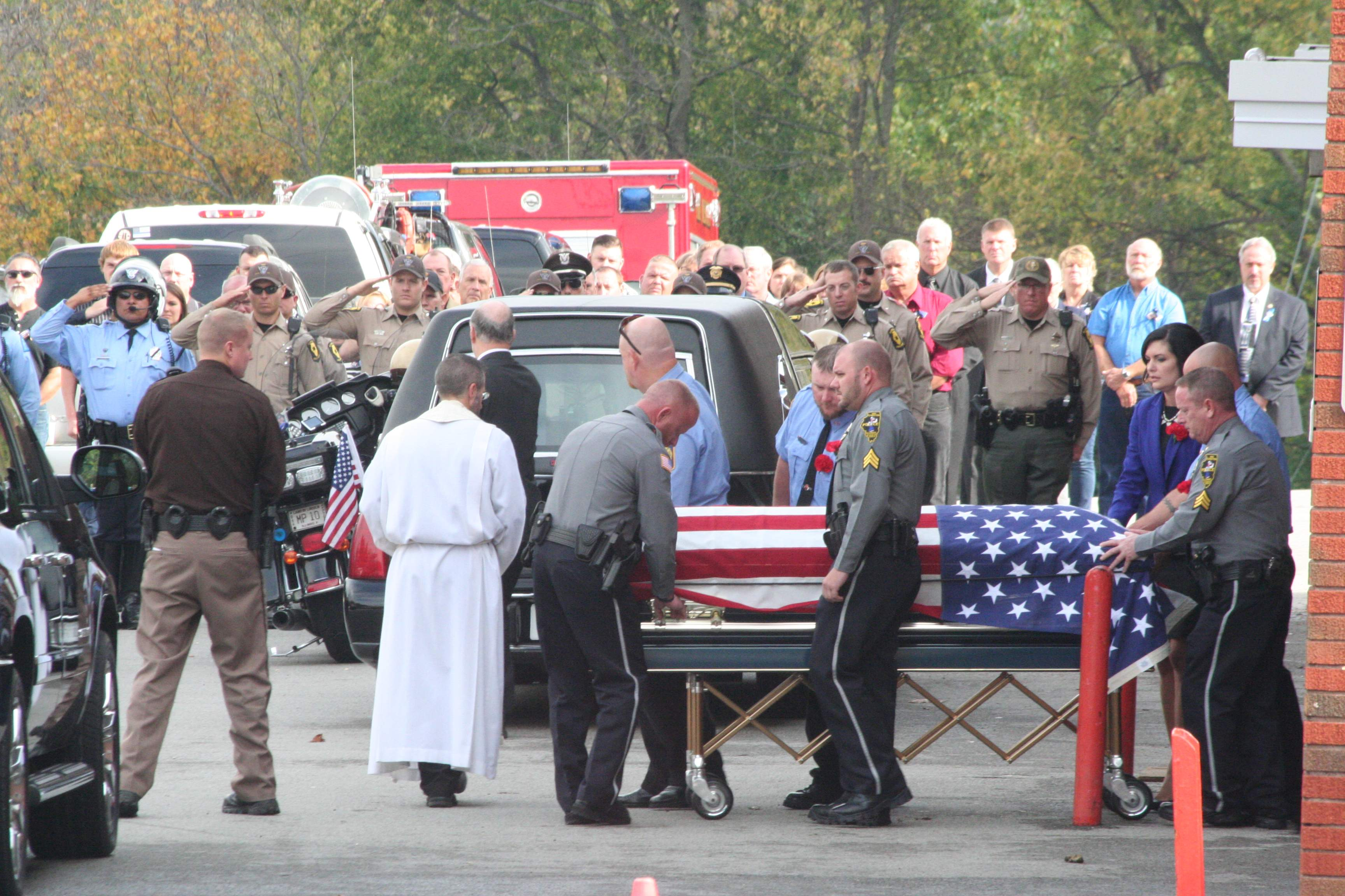 Chester police officers and firefighters escort the casket of fallen Chester Police officer and volunteer firefighter James Brockmeyer to a waiting hearse after Brockmeyer's funeral service at Chester High School in November.