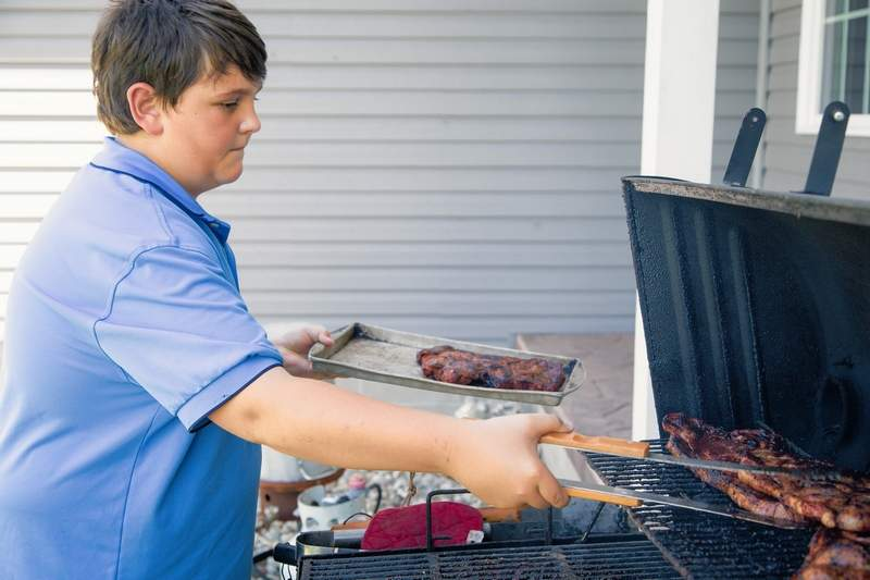 Twelve-year-old Josh Loyd of Marion, who placed first in the Food Network Kids' BBQ Championship, grills dinner for his family. Loyd took home a cash prize of $10,000 and plans to invest his earnings.