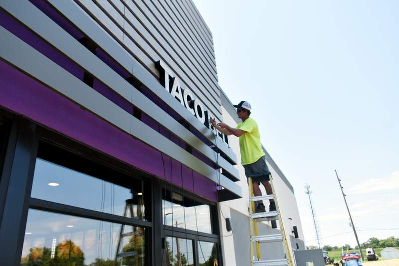 Kevin Stobart, of Piros Signs of Barnhart, Mo., installs a lighted Taco Bell sign on the outside of the new Chester restaurant in the city's Camptown section on Friday.