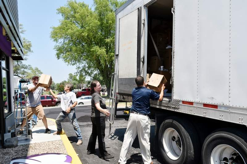 K-MAC Regional General Manager Brian Hubbard (far right) assists with the unloading of a food truck on Friday.
