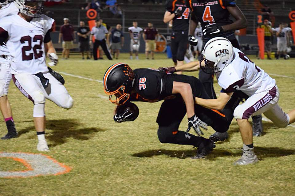 Chester's Ethan Bert stretches for extra yardage while being tackled by Carmi-White County's Jaedon Reeder.