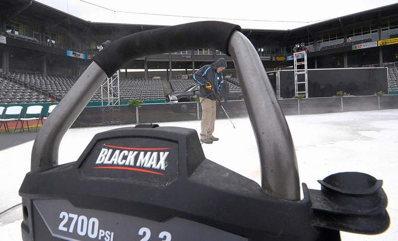 This worker sprays water over the surface of what will become an ice rink at Rent One Park in Marion.