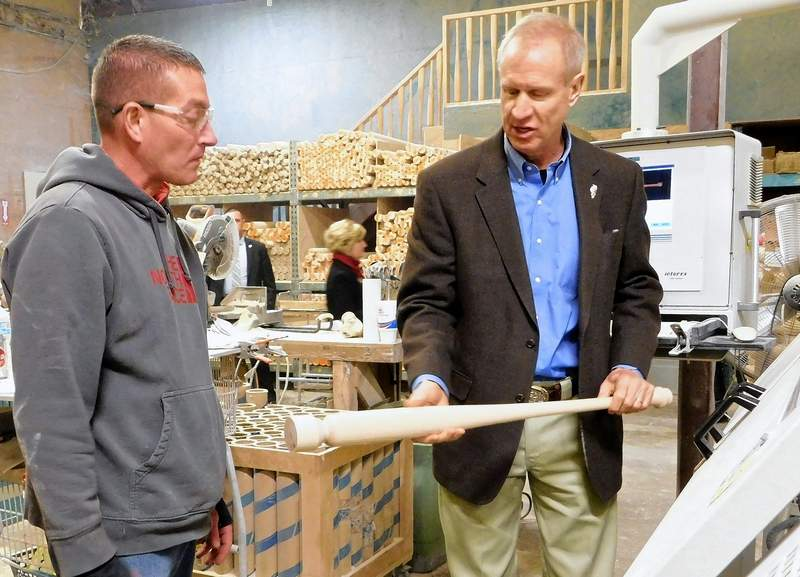 """Illinois Governor Bruce Rauner inspects a bat created by lathe operator Matt Hopson (left) during a visit to Dinger Bats in Ridgway on Thursday.  Rauner tool the unfinished bat with him.  """"I'm just going to set this in my office,"""" he said."""