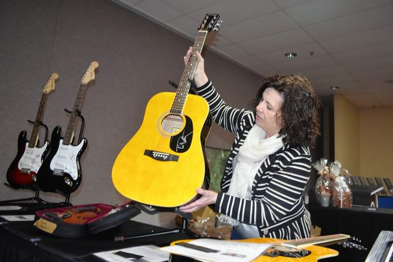 Marion Chamber of Commerce member Janet Jensen adjusts the placement of this guitar autographed by the late rock star, Tom Petty.