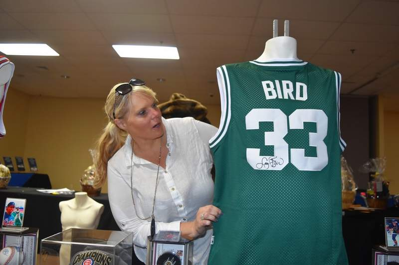 Marion Chamber of Commerce member Mary Jo McCurdy checks to see if this Larry Bird autographed jersey from the Boston Celtics is displayed prominently enough.