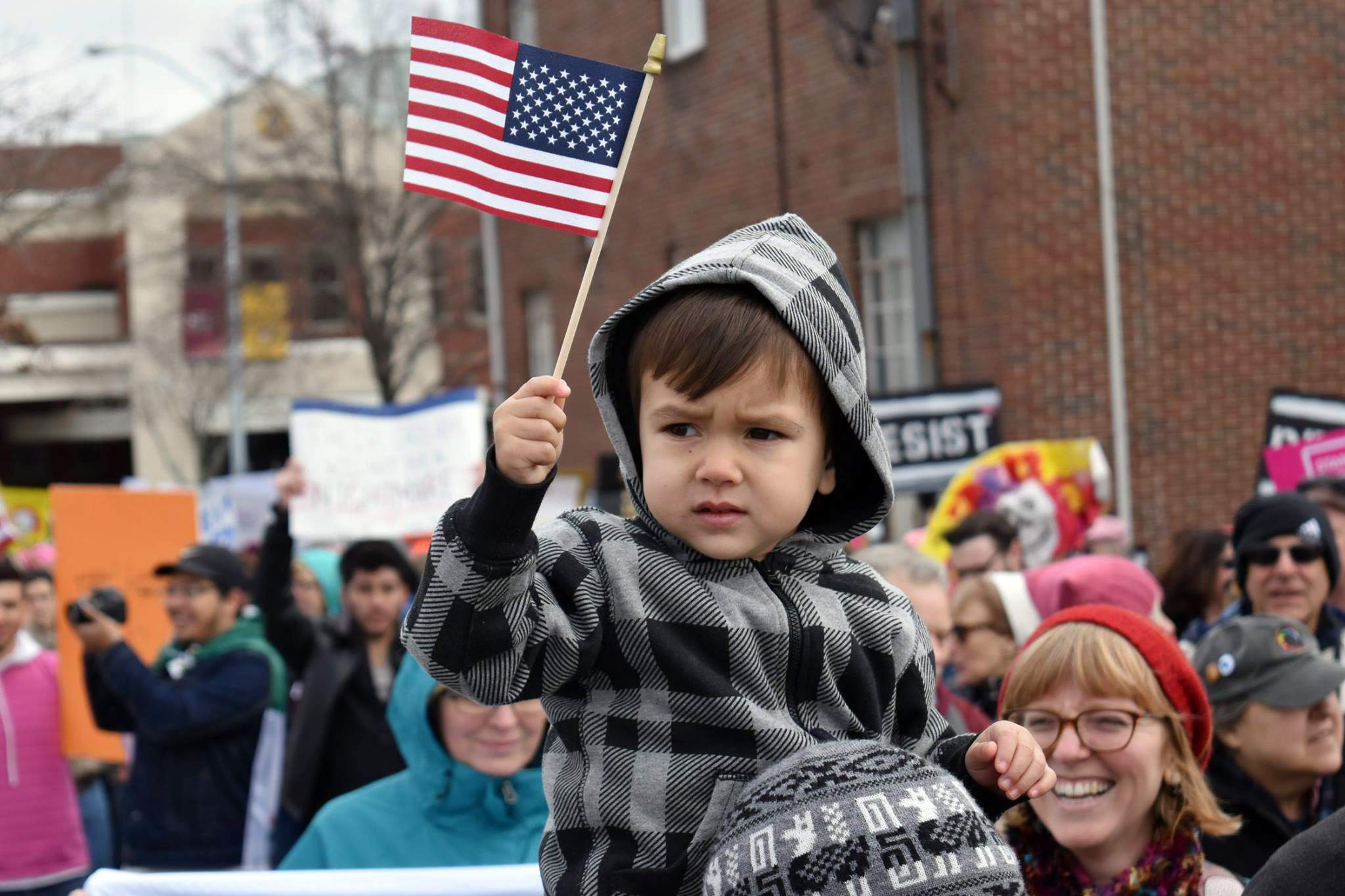 A young boy waves an American flag while perched on the shoulders of his mother during the Southern Illinois Women's March on Saturday in Carbondale.