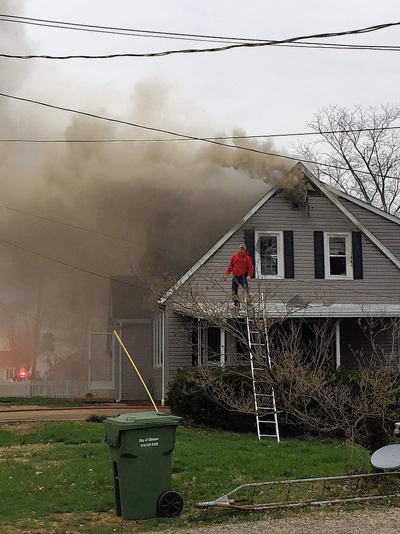 Chester Fire Chief Marty Bert breaks windows on the upper floor of a home at 1414 Allendale St. to ventilate the house.