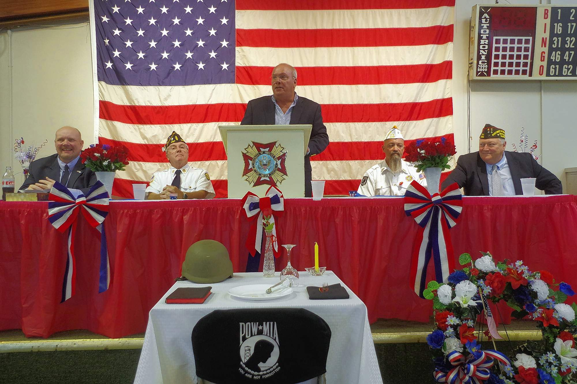 Dignitaries on stage at the 2018 Chester Memorial Day Service listen to Mayor Tom Page as he addresses a large crowd May 28. From left, Rev. Mike Fogerson of First Baptist Church in Chester; Jeff Warhausen, commander, Chester American Legion Post 487; Chester Mayor Tom Page; Tony Payne, commander of Chester VFW Post 3553; and Josh Barrett, commander of VFW District 14.