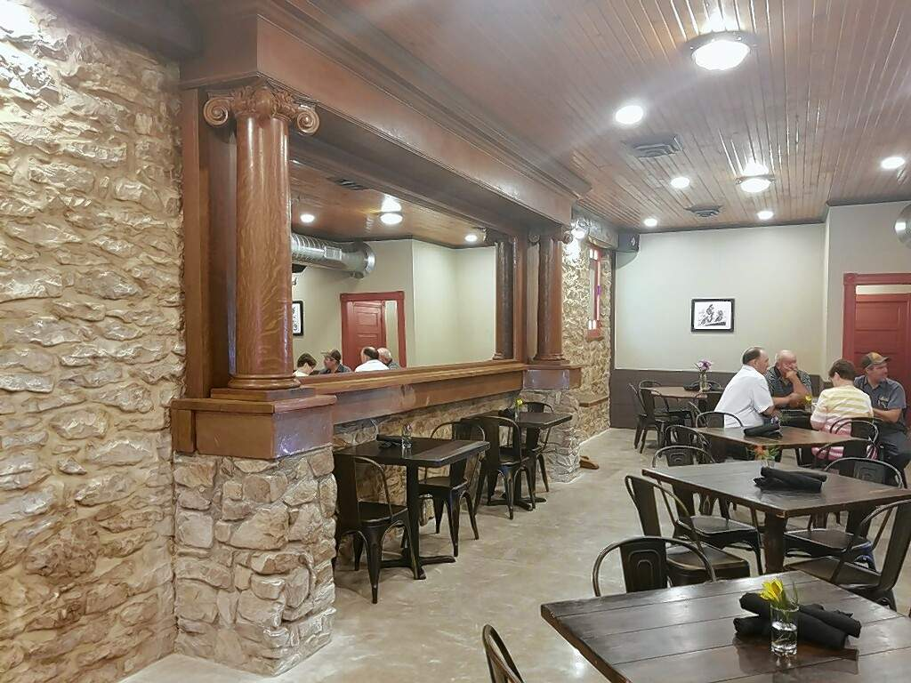 One of the downstairs dining areas of the St. Nicholas Landmark, featuring the original rock wall with a wood-framed antique mirror.