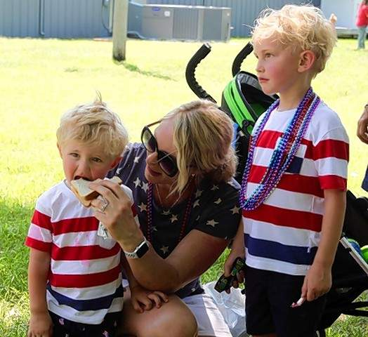 At left,  Harrison Hunter enjoys a fish sandwich with his  mom, Jules, while brother Calvin looks over the Steeleville Fourth of July picnic.  The Ainad Temple Shriners, right,  perform manuevers on motorcycles at the Steeleville Fourth of July parade.