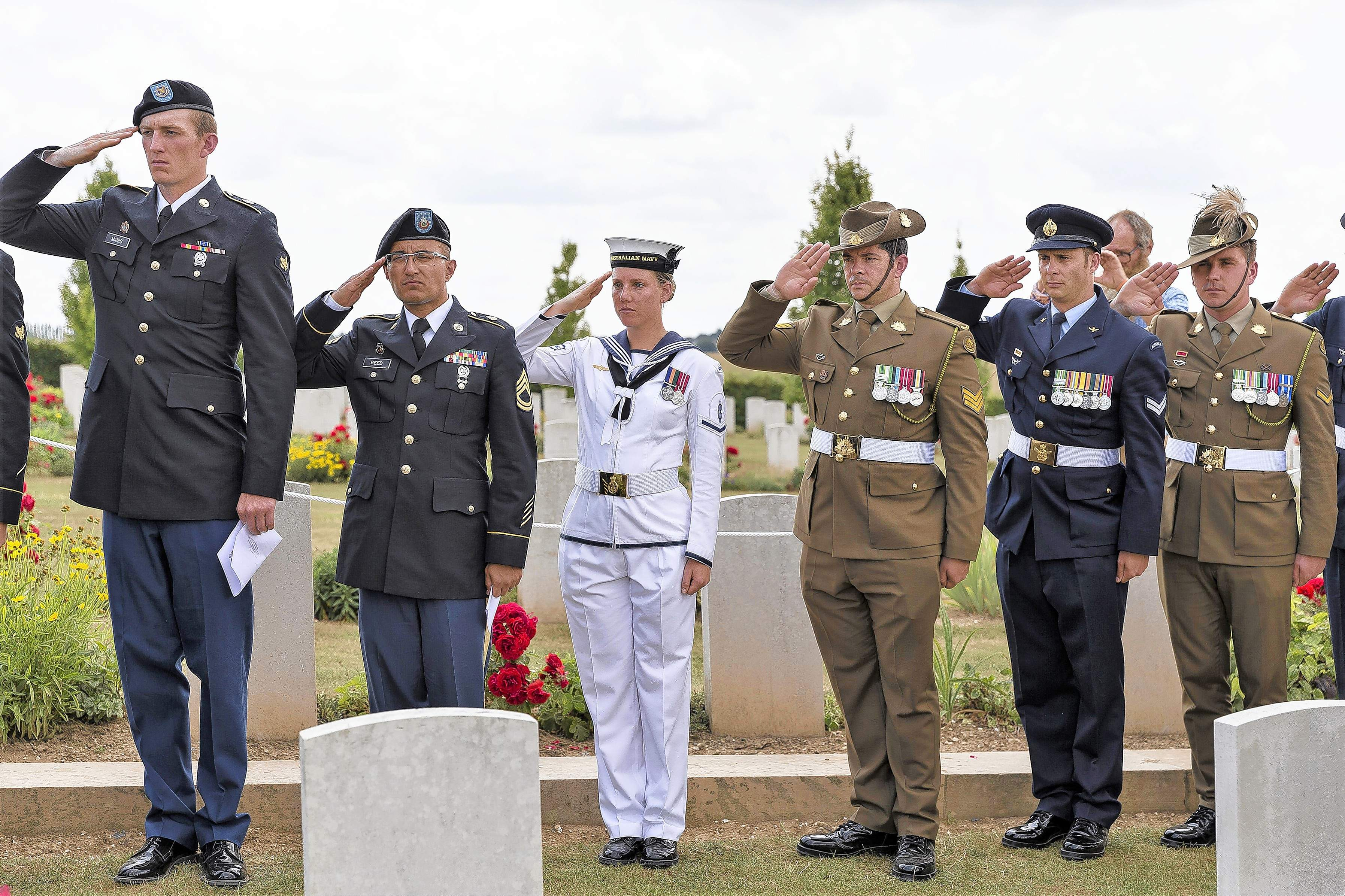 The Illinois Army National Guard's Spc. Troy Mairs of Ashton, left, and Sgt. 1st Class Robert Reed of Sparta salute with Australian service members during a headstone rededication conducted for Australian Army Private Robert Bowness on July 4, 2018, at Villers-Bretonneux Cemetery in France. Bowness, a member of Australia's 4th Pioneer Battalion, was killed on the Western Front 100 years ago