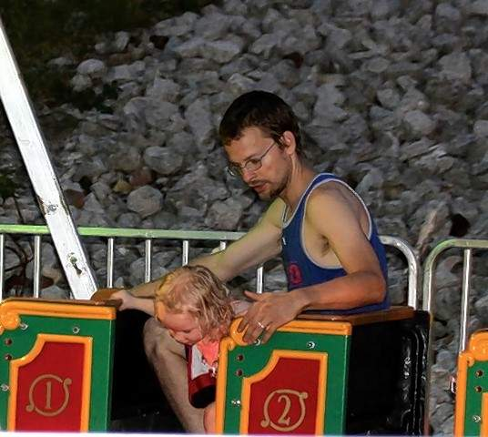 Dan Zobel and his daughter Ezraih ride the train at the 39th Annual Popeye Picnic carnival.