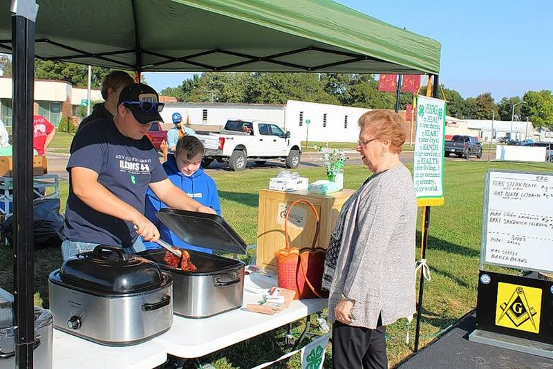 Riley and Chace Smith of Ruma serve food at the Randolph County Federation Club BBQ fundraiser in Red Bud.