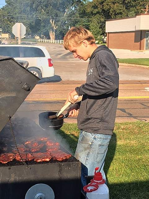 Matthew Koester of Red Bud helps work the grill.