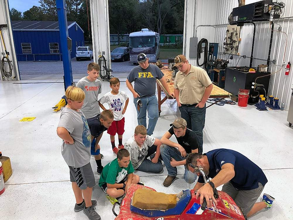 Above, Cody Mavert, Dillon Swisher, Braydon Swisher, Nick Rubach, Camden Pierce, Matt Murray, Riley Smith, Dominic Neal, and Harris Ehlers watch leader Matt Mavert at a recent meeting of the Small Engine 4-H Club.  Matt Mavert, owner of Mavert Automotive & Tire Center, became a new 4-H leader to teach Randolph County youths about small engines. At right, the students gets some hands on experience with engines, under Mavert's guidance.