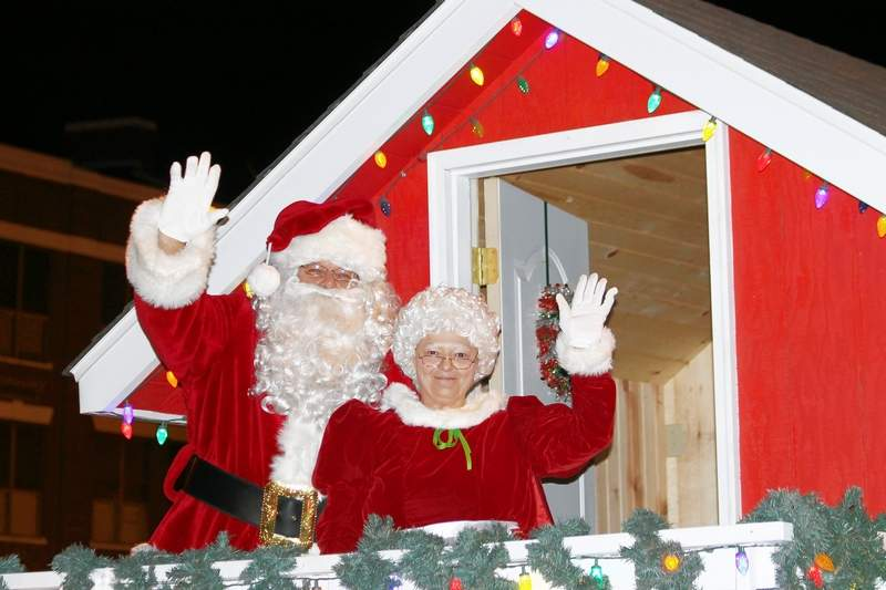 Santa and Mrs. Claus wave from their cottage atop a float in last year's Christmas on the River Lighted Parade.