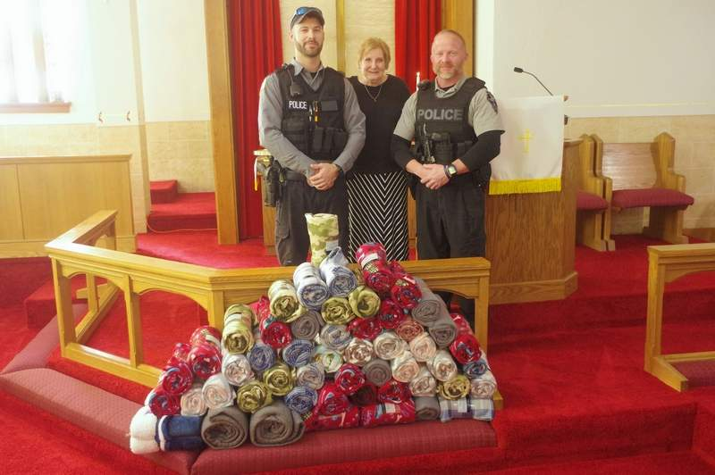 Officers Jeff Hammel, left, and Joe Crain, right, accept the donation of blankets on behalf of the Chester Police Department. Making the presentation is Pastor Faye Edmaiston.