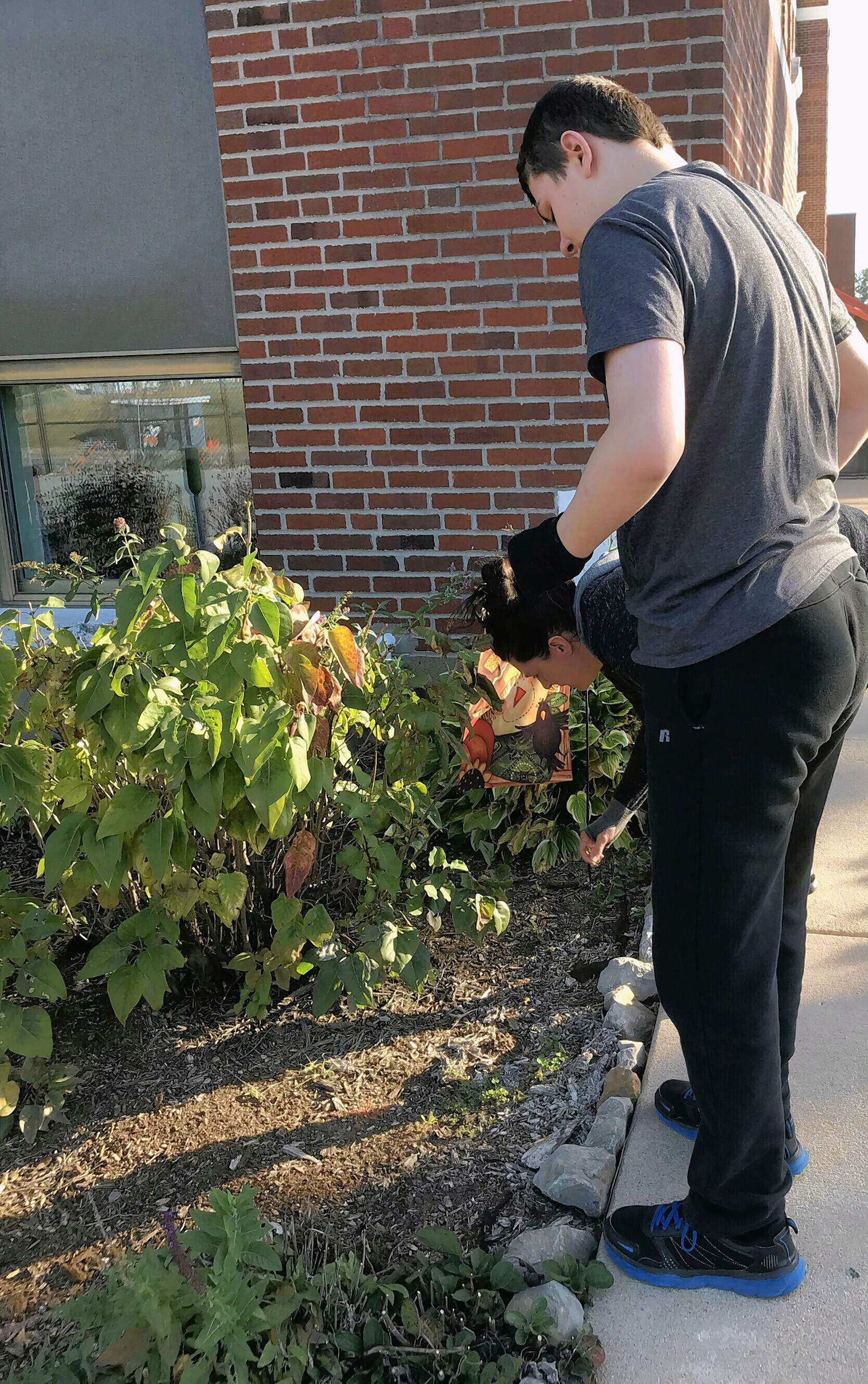 Student Jeffrey Dobyns works in the garden, with paraprofessional Tisha Coffey to his right.