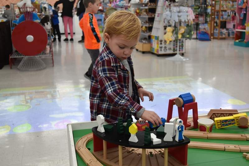 Cooper Smith, 2, of Carterville, enjoys playing with this train set Saturday at Jack and Josie's toy store in Marion.
