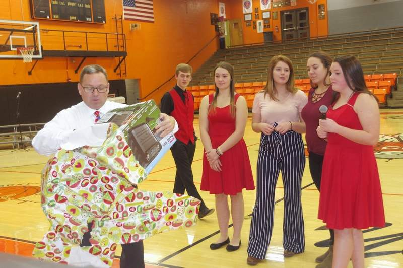 CHS senior music students, from left, Jacob Wingerter, Vanessa Inman, Jadi Richards, Lexie Price and Caitlin Elsea watch as Steve Colonel, CHS Band and Choral Director opens gifts from the CHS Band and Choral students.