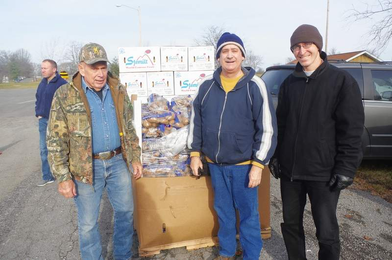 From left, volunteers Bob Decker, Steve Simpson and Justin Massey prepare to distribute food to clients at the December Mobile Market.