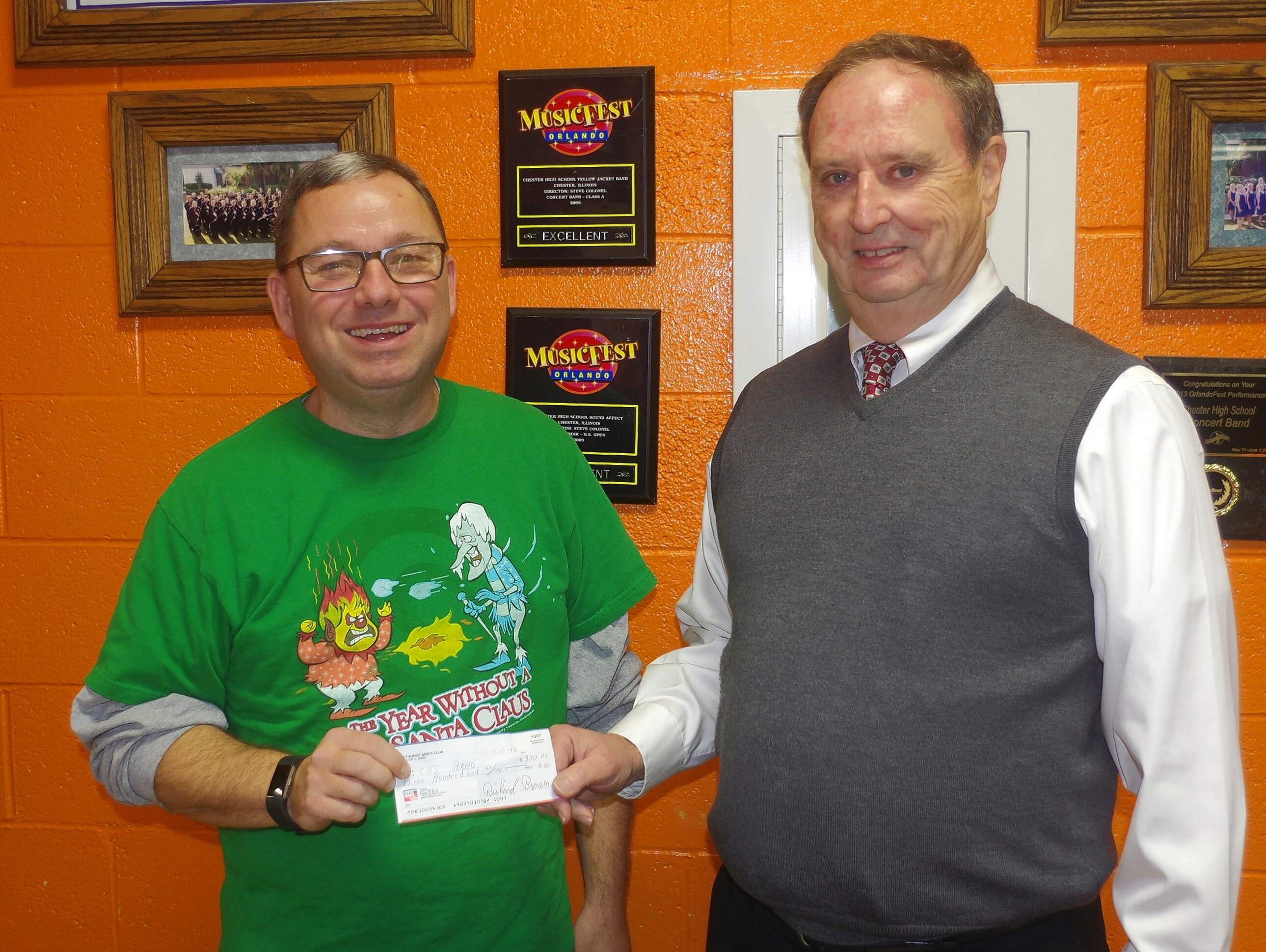 Judge Richard A. Brown, the Methodist Men's treasurer, right, hands the $300 donation to Steve Colonel, Chester High School music director.