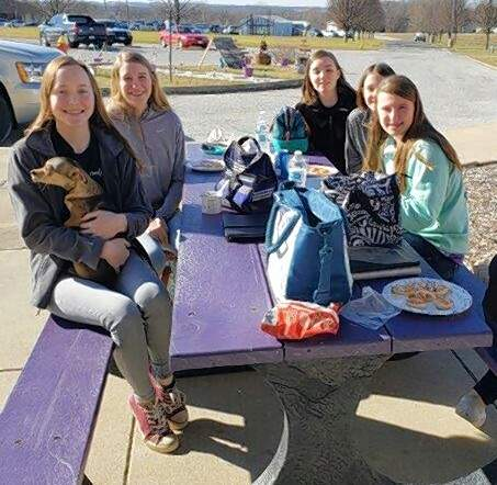 Students at Christ Our Savior High School enjoy the new outdoor lunch table.