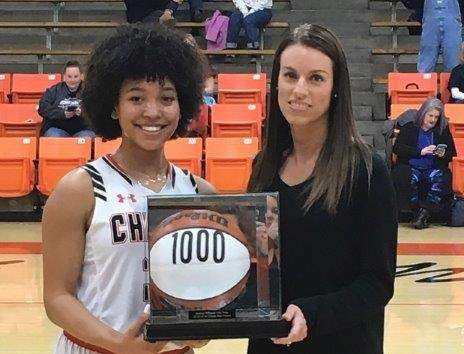 Destiny Williams, left, receives her 1,000-point trophy from Jennifer Knowles-Coleman, the only other Lady Jacket to ever score 1,000 points.