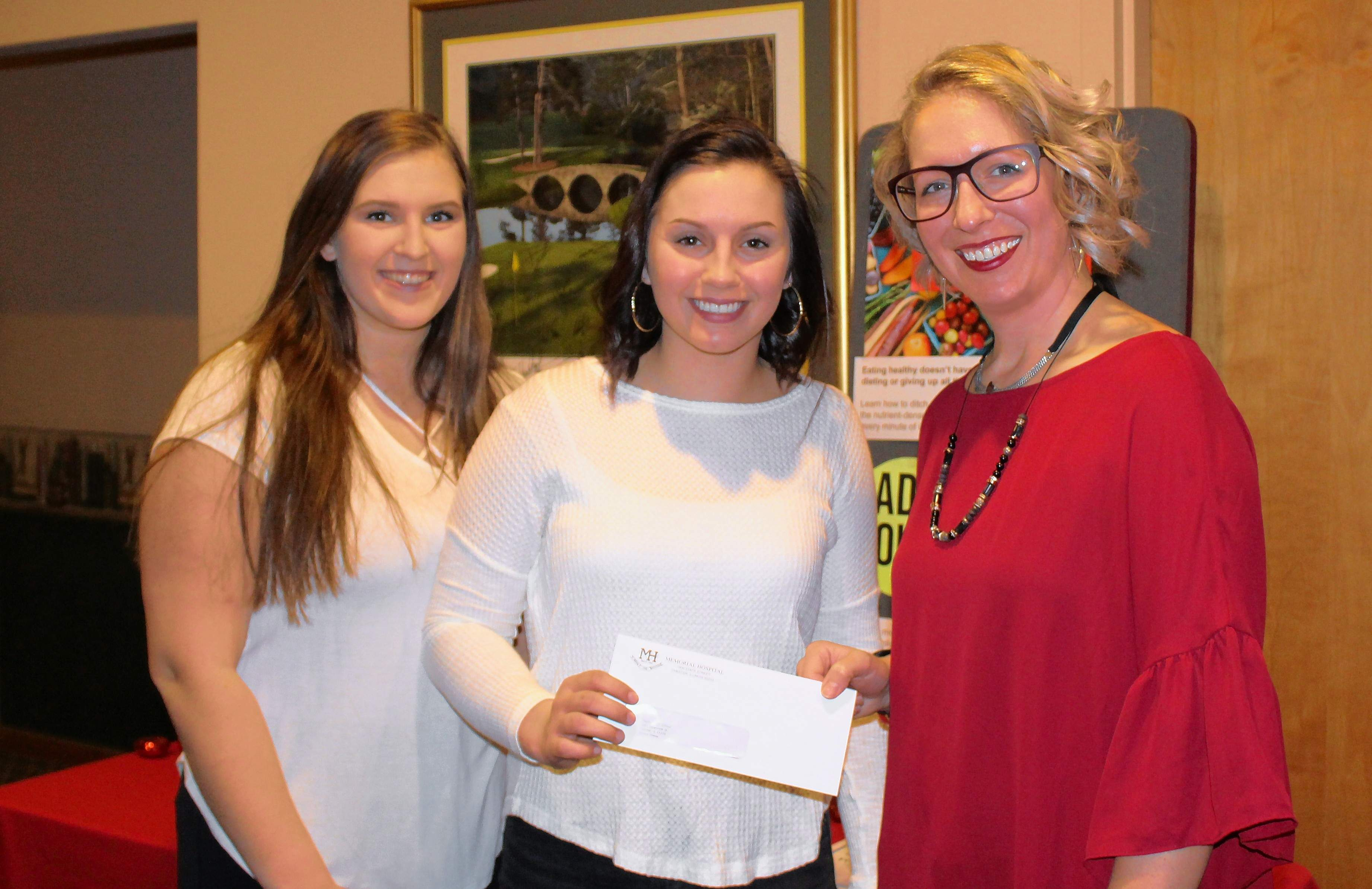 From left, National Honor Society students Lauryn Vasquez and Shea Petrowske with Mariah Bargman, community relations coordinator for the hospital.