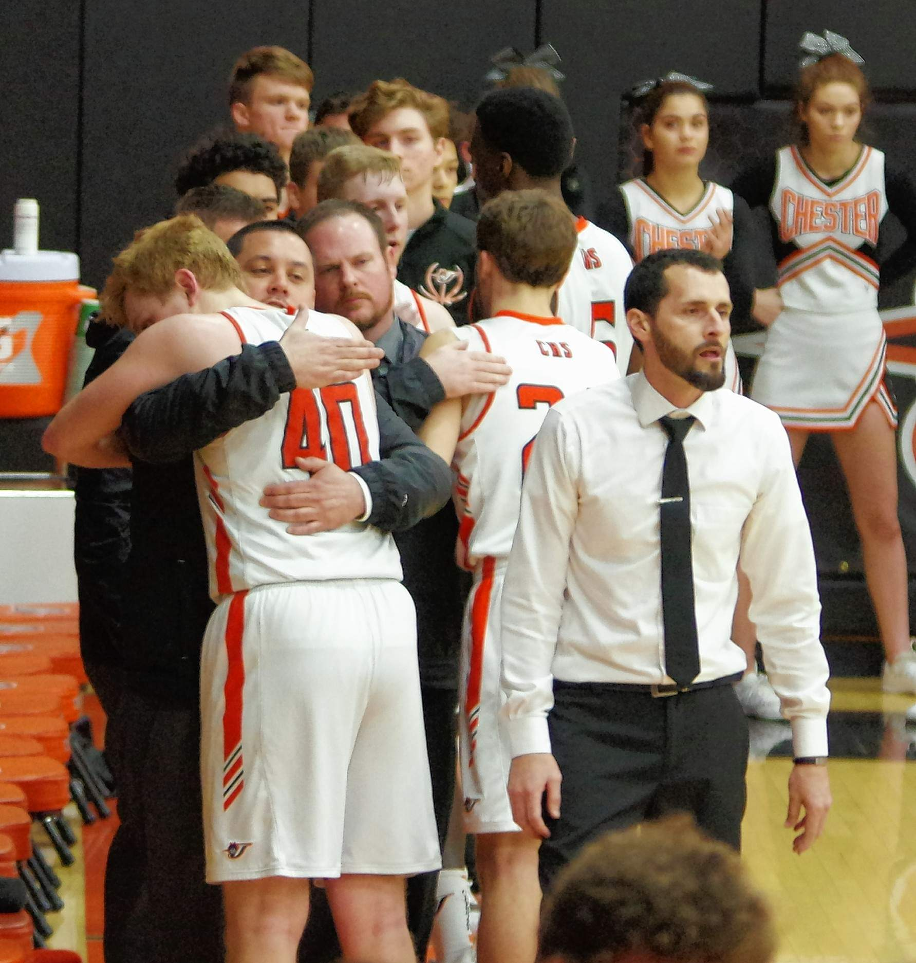 Chester High School senior Drake Bollman (40) comes off the floor for the final time of his high school career and gets a huge hug from CHS Assistant Coach Chris Toledo.