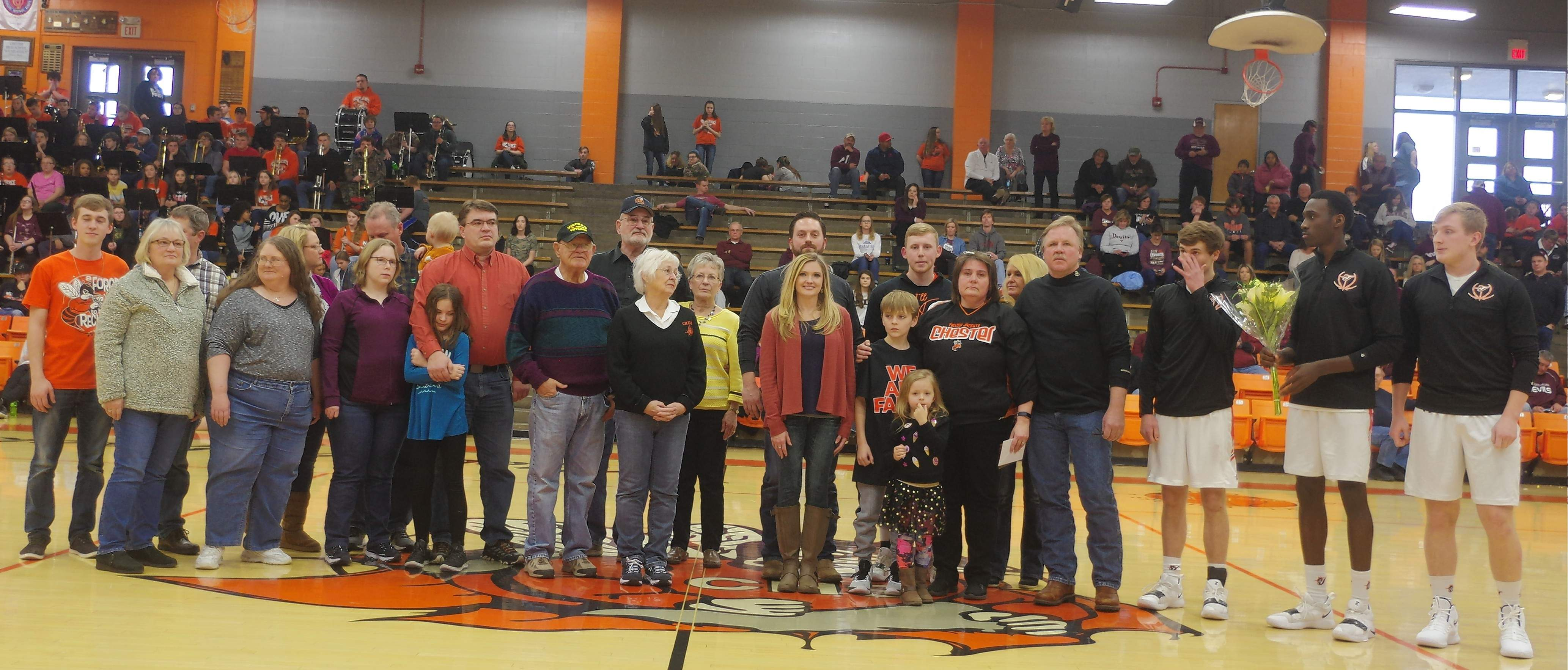 Players Keith Kiner III, Drake Bollman and Colin Wingerter, far right, present the Link family with a plaque of appreciation.