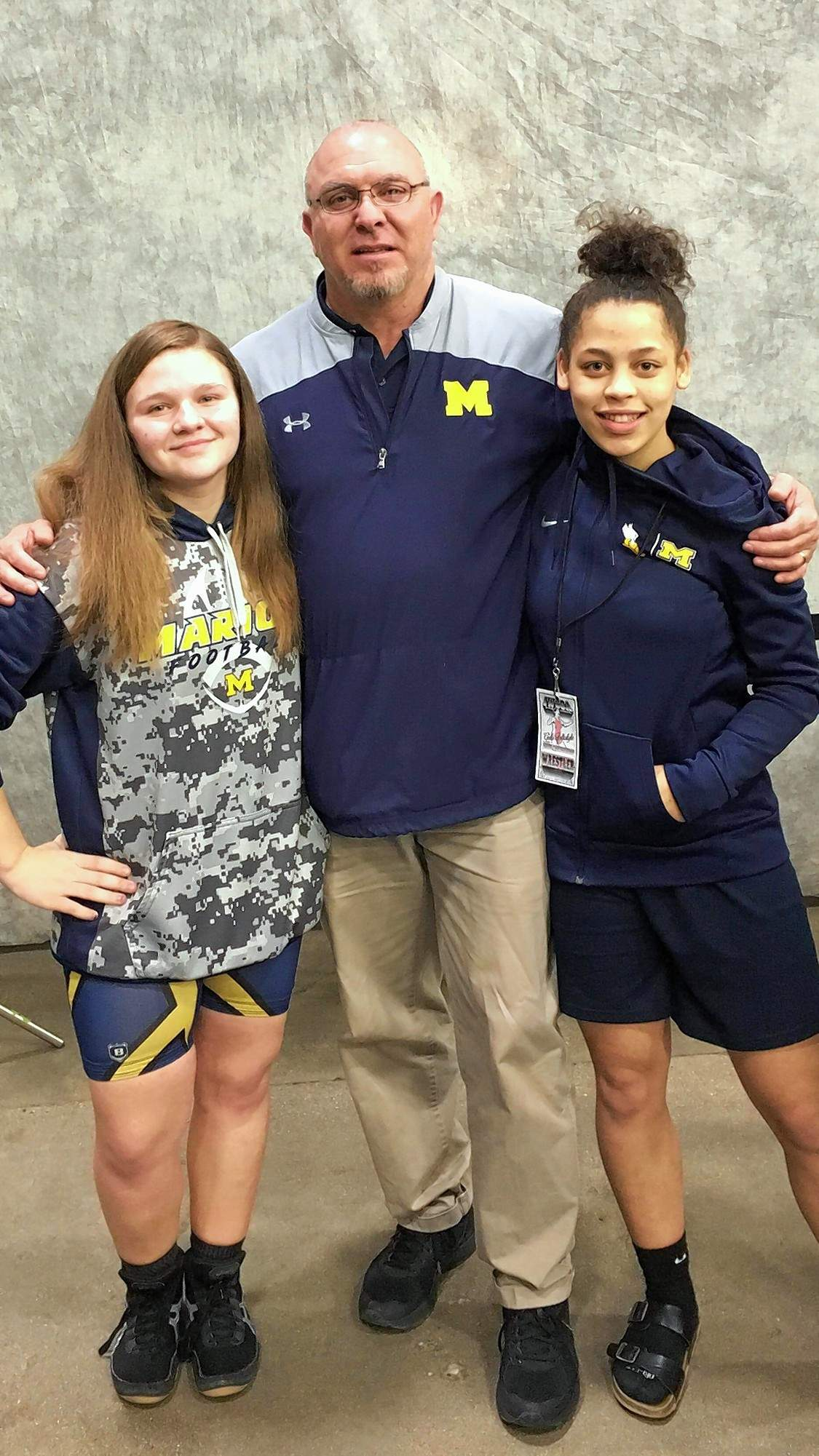 Marion High School wrestling coach Darren Lindsey is shown here with his first two female wrestlers - Jade Napier and Emma McGee, who both  qualified for a state meet.