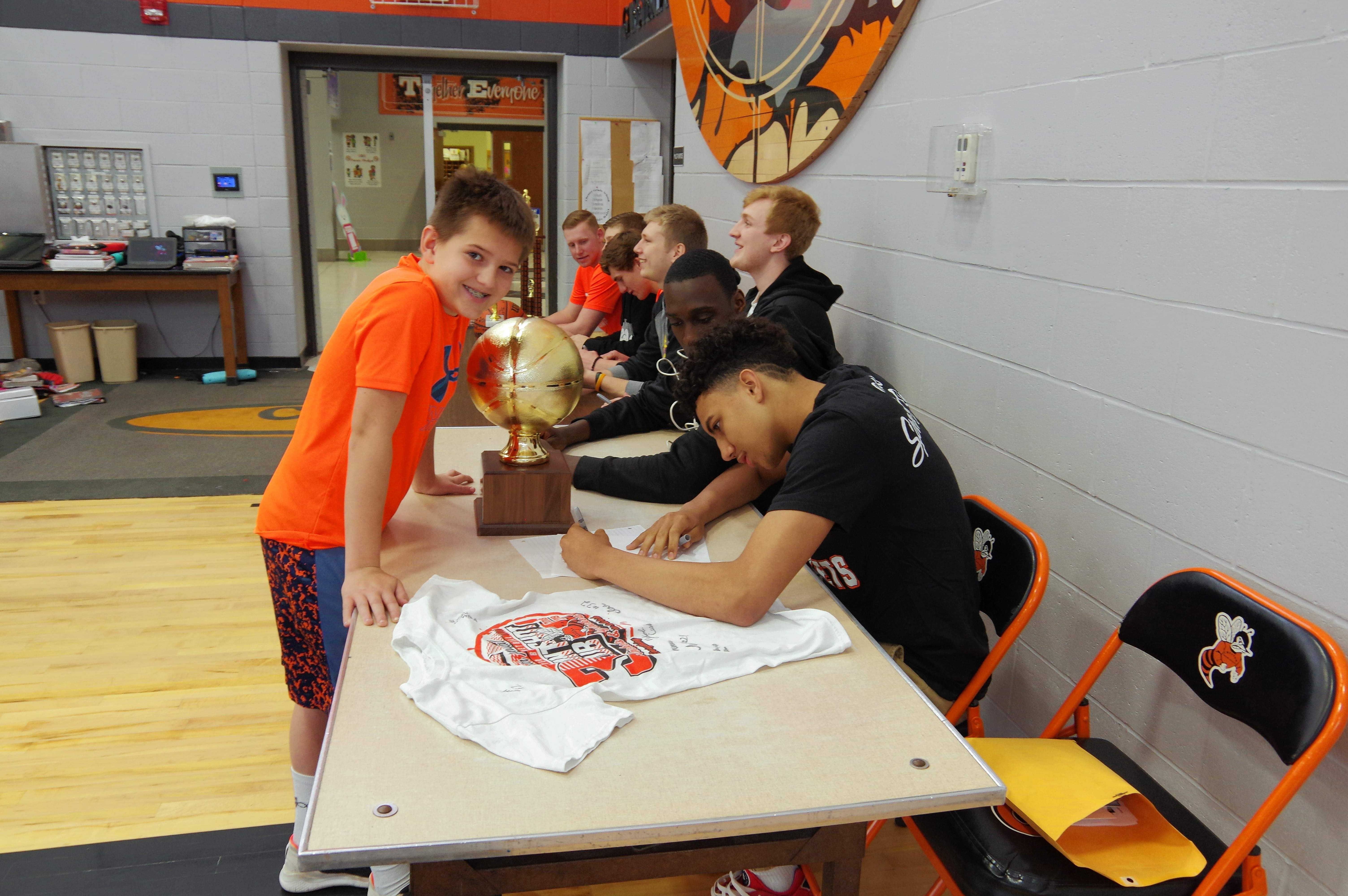 Fifth grade Lannin Carter is the first in line to get autographs. Signing Lannin's team photo is DeOndre Martin.
