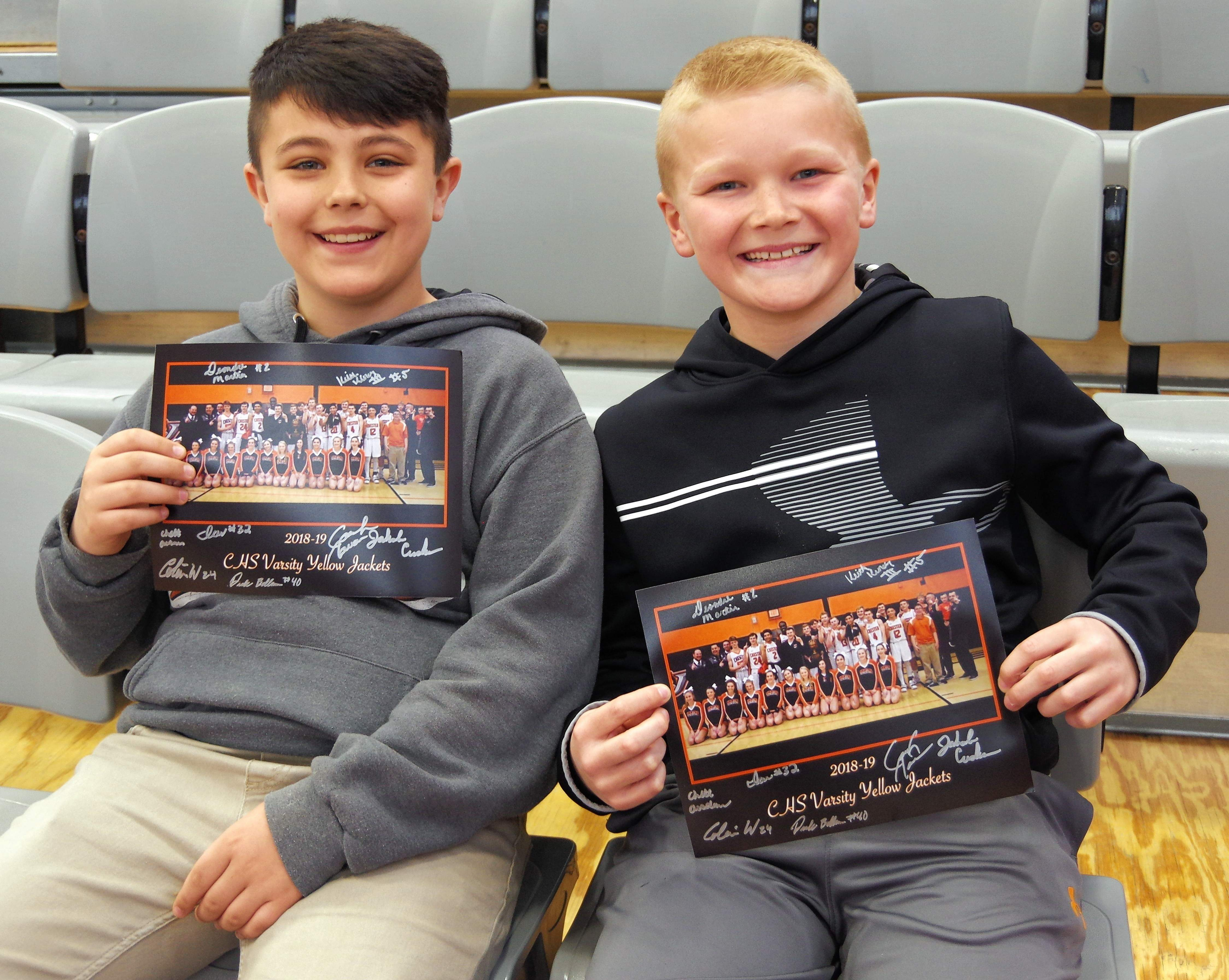 Fifth graders Caleb Richmond, left and Trayton Peters proudly show off their autographed CHS Varsity Basketball team photos.