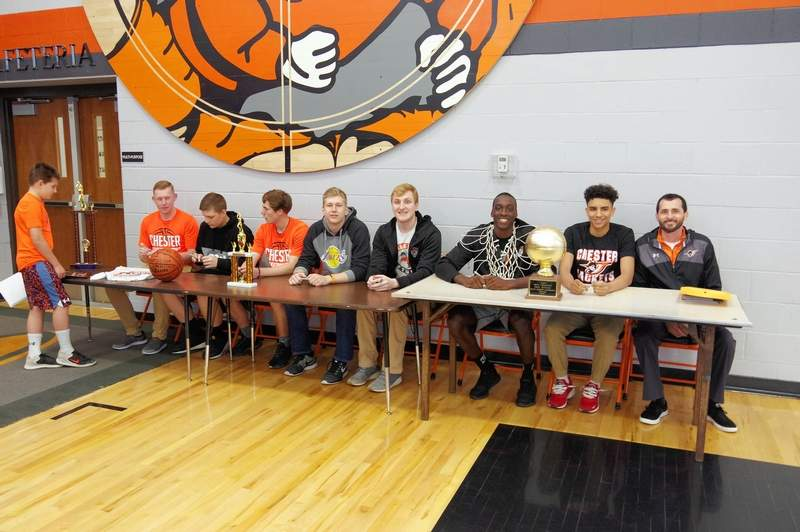 Basketball players smile for the camera about 10 seconds before they were mobbed by grade school kids. From left, they are Jakob Cushman, Chett Andrews, Colin Wingerter, Ian Reith, Drake Bollman, Keith Kiner III, DeOndre Martin and Head Basketball Coach Brad Norman.