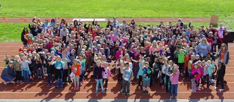 The 1st- through 5th graders and their teachers wave from the track at the end of Fitness Day.