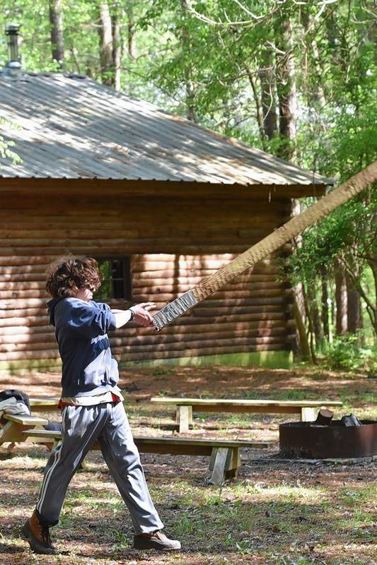 Wilson DeNeal of Harrisburg Troop 23 throws a wooden beam for the caber toss during the Spring Camporee Highland Games at Pine Ridge Scout Camp near Makanda.