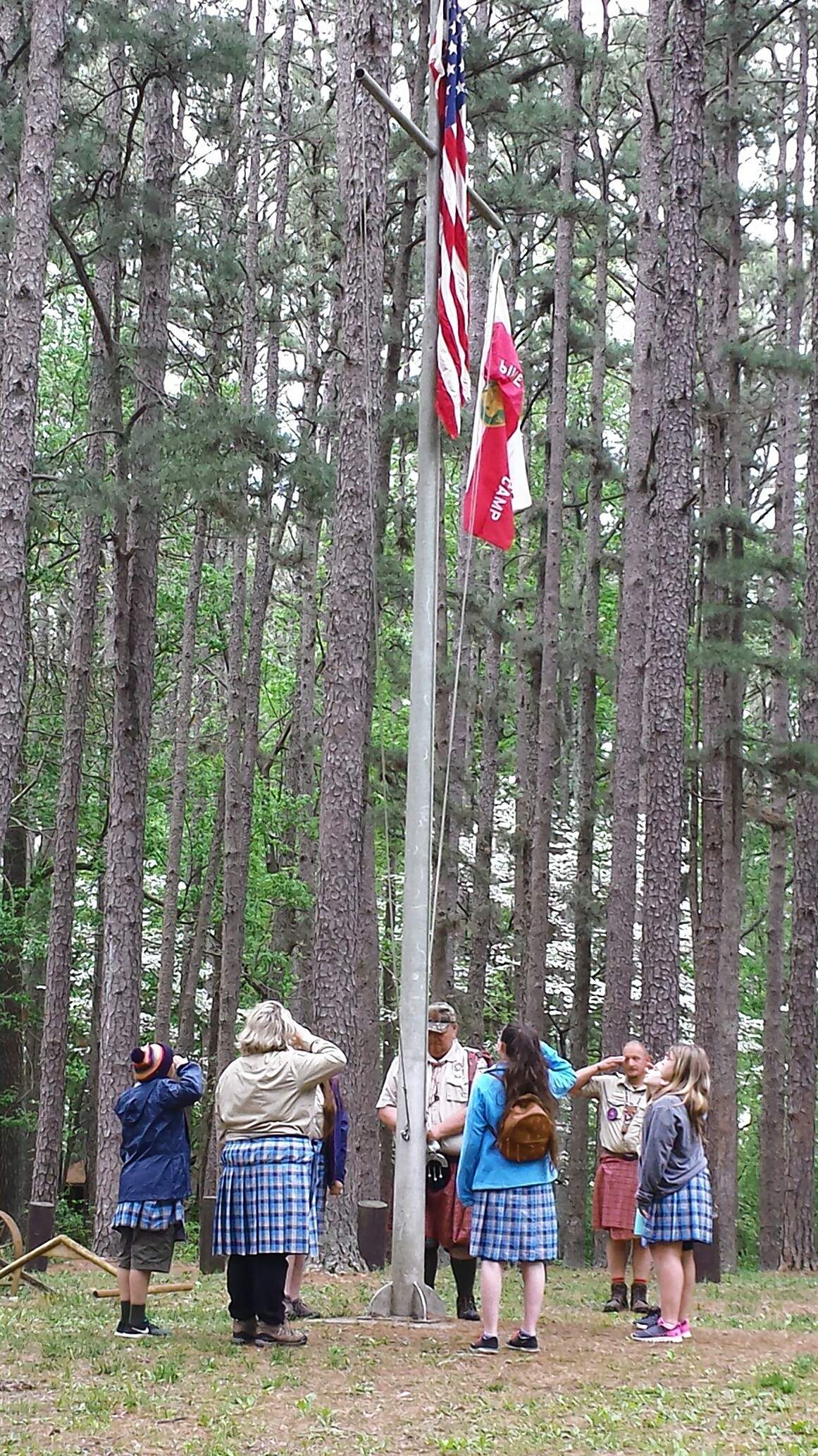 TRAVIS DENEAL PHOTOMembers of Scouts BSA Troop 156G of Christopher salute the flag at the opening ceremonies of the Spring Camporee Highland Games at Pine Ridge Scout Camp. The all-girl troop had the honor of raising the flag at the ceremonies.