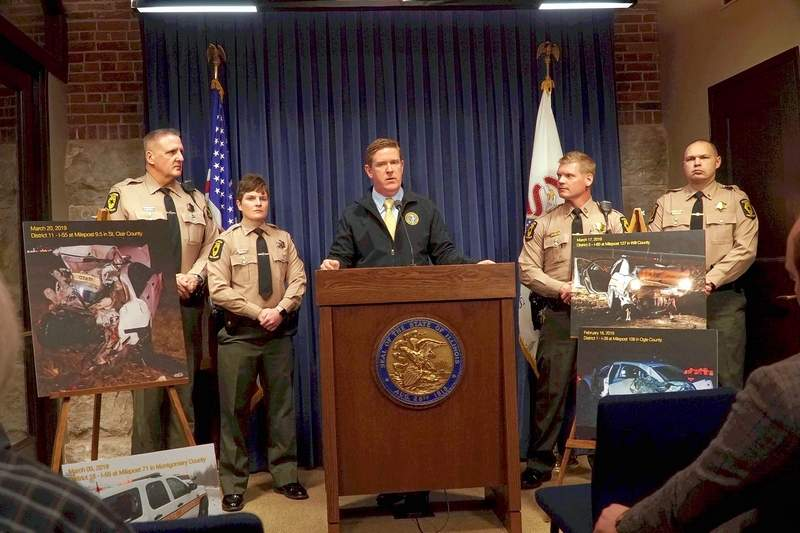 "Flanked by fellow Illinois State Police personnel and photos of crashes involving motorists striking parked squad cars, acting ISP Director Brendan Kelly speaks during a news conference March 26 in Springfield. Kelly talked about an ""extremely concerning"" increase in the number of incidents of moving vehicles colliding with parked police cars and officers along Illinois roads."