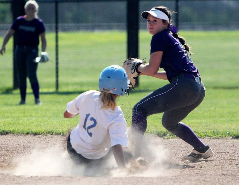 Harrisburg's Hannah Reid looks to turn this double play as Pinckneyville's Kiya Hagene slides into second base during Friday's Class 2A Sectional Championship at Du Quoin High School.