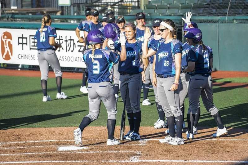 Erika Polidori of the Canadian Wild of Southern Illinois is congratulated as she reaches home plate by her teammates. The Wild swept a six-game series from the Beijing Shougans Eagles, better known as the Chinese national team last week in Florida.
