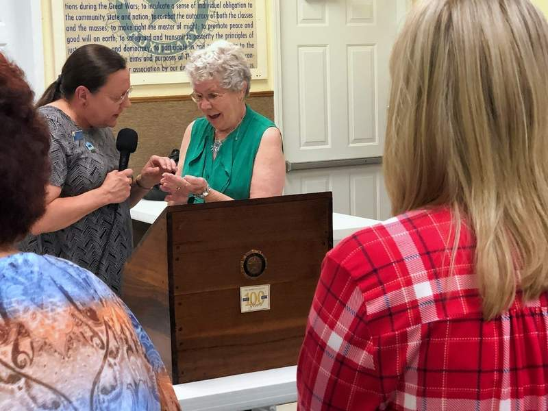 Freda Broadway, right, is presented with a commemorative coin in recognition of her outstanding work and leadership for the American Legion Auxiliary.