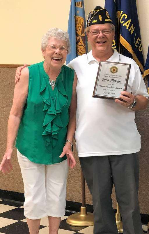 Freda Broadway, left, and John Metzger share a laugh after Broadway presented Metzger with a 'self not service' award from the American Legion Auxiliary for his years of service.