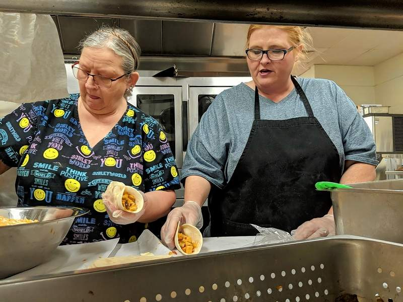 CES 95 food services summer meal workers Sharon Rawls (left) and Danielle Blythe stack the shredded chicken mixture and cheese toppings onto the chicken fajitas they made June 4, the first public day of District 95's Summer Meal program.