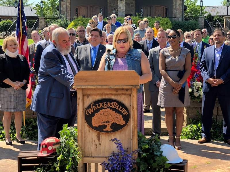 With husband Dave looking on, Walker's Bluff owner Cynde Bunch addresses a crowd gathered at the venue Tuesday morning.