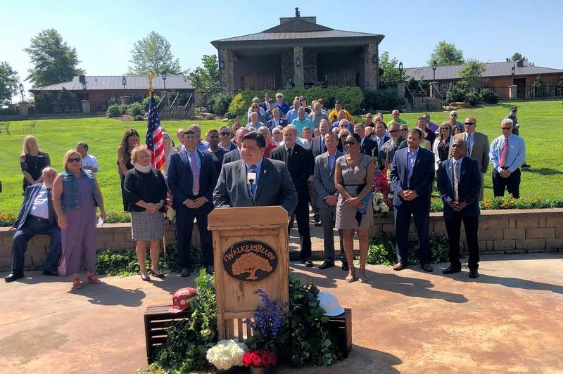 Gov. J.B. Pritzker addresses a crowd gathered at Walker's Bluff Tuesday morning, making official the Illinois Gaming Bill that will allow for the much-anticipated resort project.
