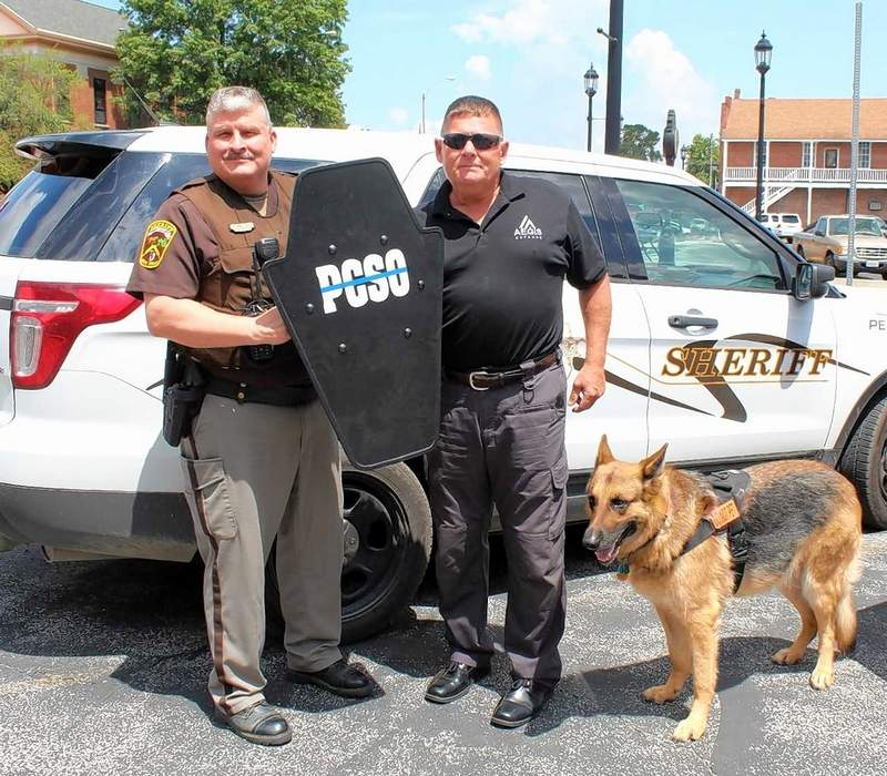 Perry County Sheriff Steve Bareis (L) was presented with a ballistic shield by Jack Queen of AEGIS Tactical Defense, a non-profit organization that purchases shields to donate to schools, churches, hospitals, and law enforcement groups. Also pictured is Tess, a canine officer.